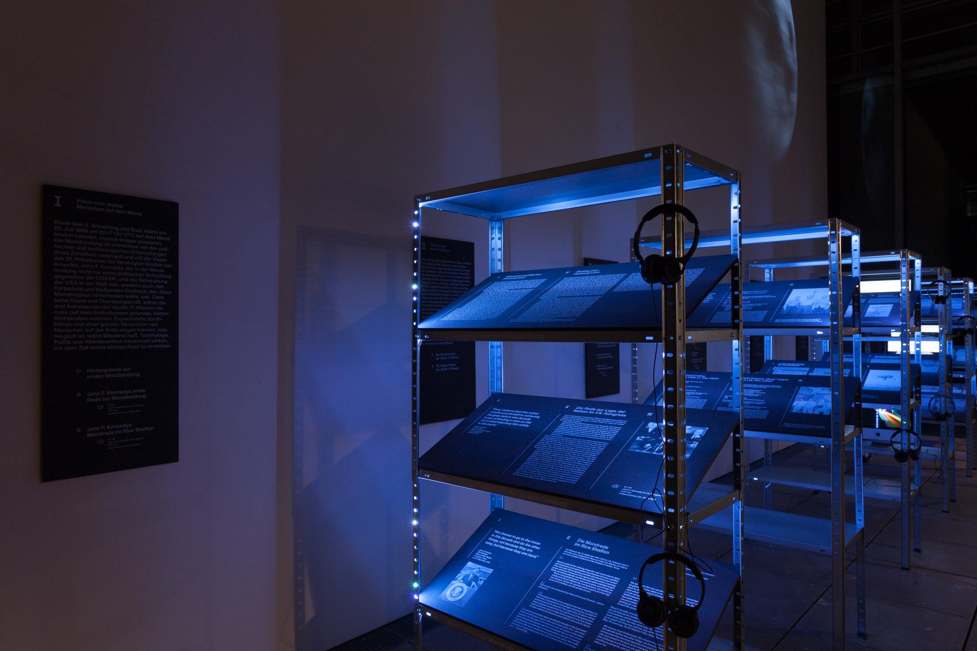 Schwerlastregale wurden zu Ausstellungsmöbeln umfunktioniert die als Informationsträger Grafik im Raum inszeniert haben.