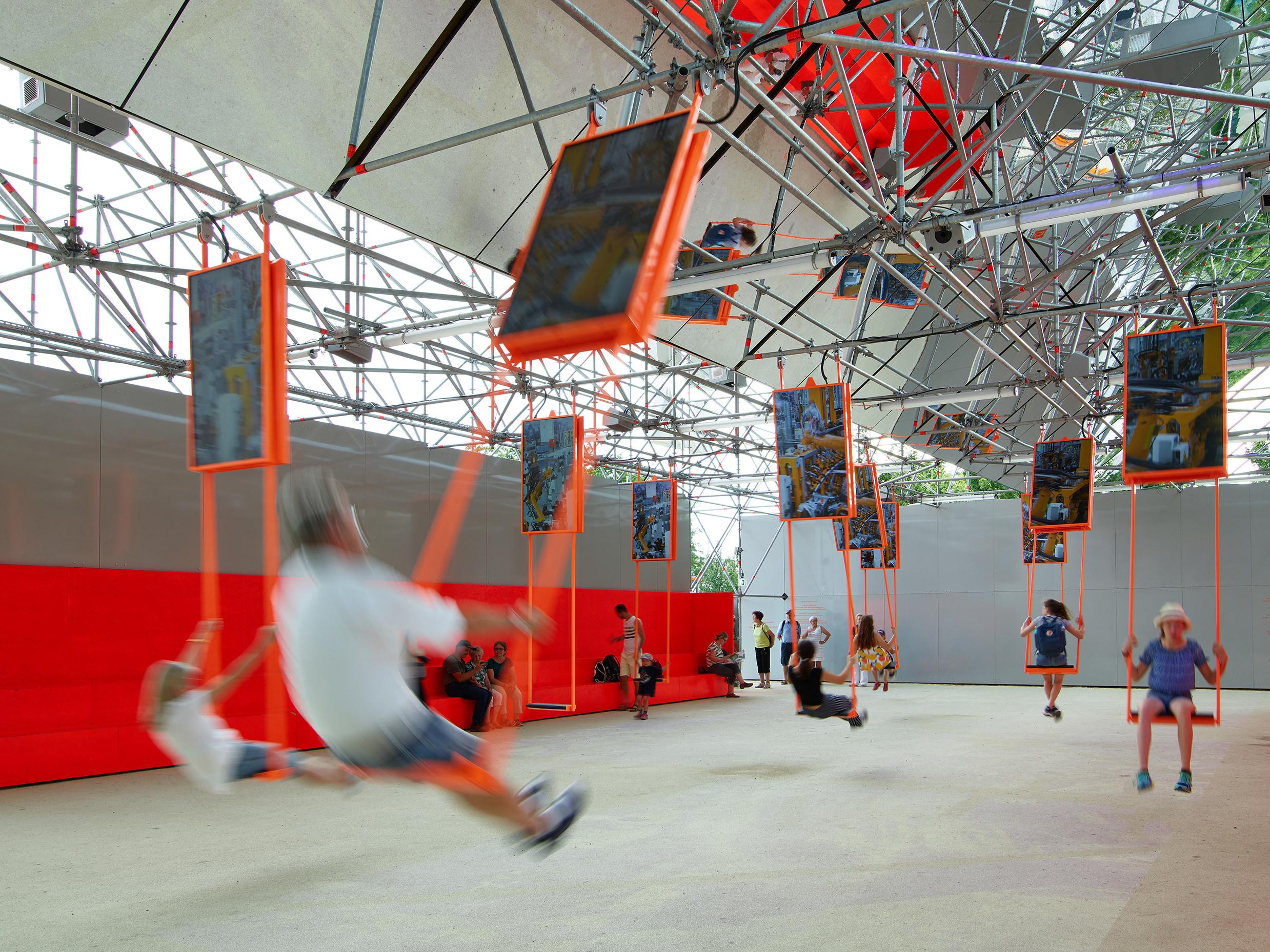 Impressionen des Pavillon auf der BUGA 2019 in Heilbronn. Die Besucher:innen sind in Bewegung auf den Medienschaukeln, die atmosphärische Inhalte und Interviews zeigen.